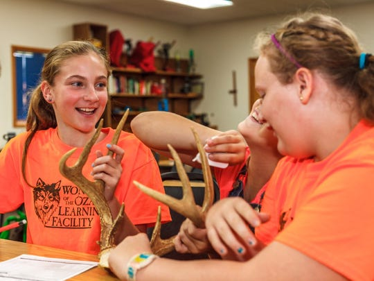 """Jenna Perryman, left, practices measuring a set of deer antlers during a recent """"deer camp"""" lesson — part of her WOLF school 5th grade class."""