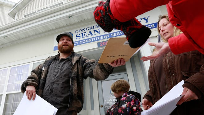 Organizer Joel Lewis, of Wausau, from Citizen Action of Wisconsin, passes around a clipboard for signature Tuesday afternoon, January 24, 2017, at Congressman Sean Duffy's office on Grand Avenue in Wausau.