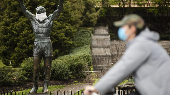 A cyclist wearing a protective face mask as a precaution against the coronavirus moves past the Rocky statue outfitted with mock surgical face mask at the Philadelphia Art Museum in Philadelphia, Tuesday, April 14, 2020. (AP Photo/Matt Rourke)