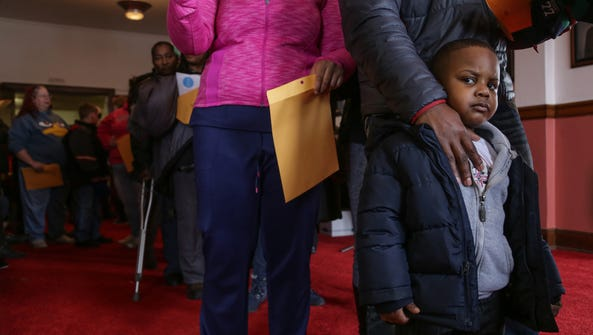 Jaylen Smith 4 of Flint waits in line with his father