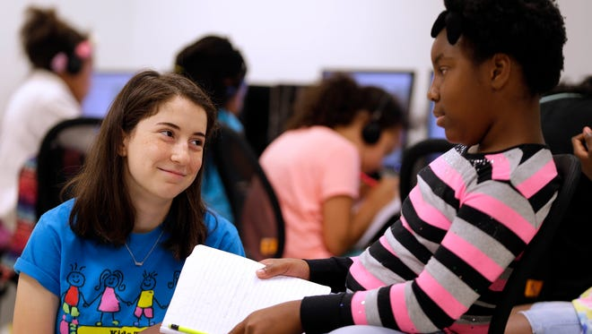 Katie Eder (left), a senior in high school, smiles at an answer from Keisha Walton, 10,  as Eder teaches Kids Tales, a summer workshop on creative writing for children at the COA Youth and Family Center during summer camp.