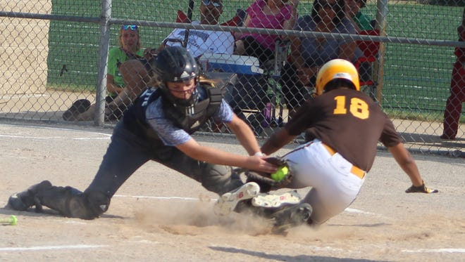 Farmington's freshman catcher Lily Morrissette tags out North Farmington base runner Autumn Bulmer (18) on a close play at the plate in the second inning of Tuesday's pre-district clash.