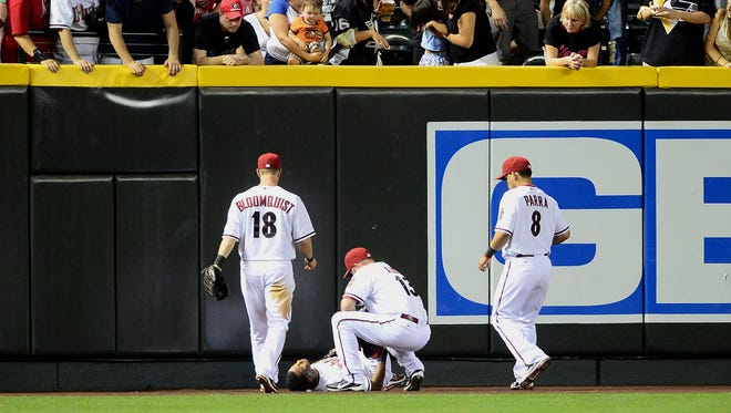 Diamondbacks teammates tend to outfielder Chris Young, who injured his shoulder crashing into the Chase Field wall to make a catch against the Pittsburgh Pirates on April 17, 2012.