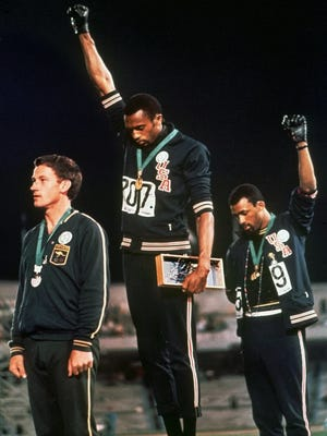 In this 1968 file photo, U.S. athletes Tommie Smith, center, and John Carlos, right, stare downward while extending gloved hands skyward during the playing of the Star Spangled Banner after Smith at the Summer Olympic Games in Mexico City.