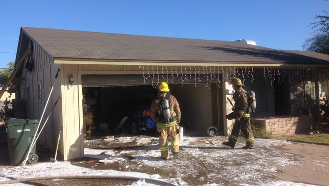 Phoenix firefighters clean up after a fire near 15th Avenue and Bell Road on Dec. 29, 2014.