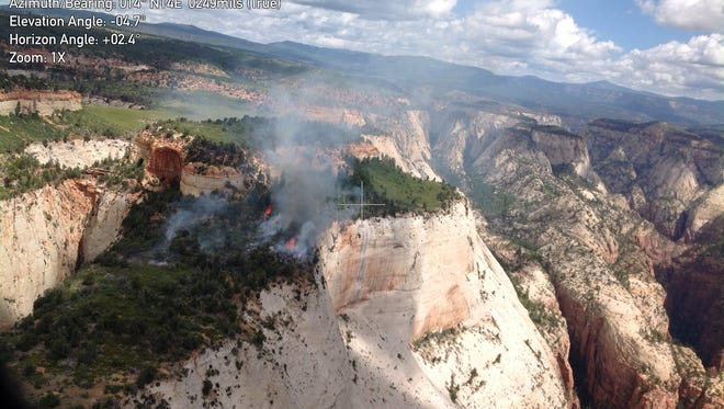 The Cathedral Fire burns along a mesa top in Zion National Park.