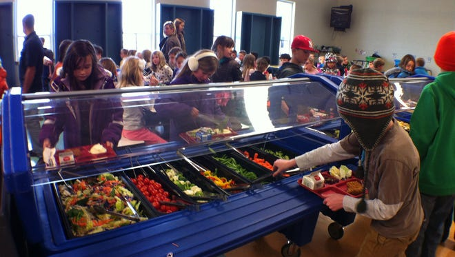Students at Zach Elementary in Fort Collins pick and choose fruits and vegetables from the produce bar during a meal. The fruit and vegetable bar is a fixture at all schools in the district.