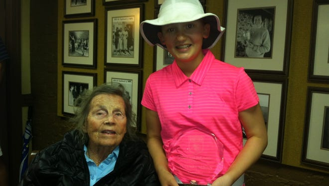 Junior golf star Nicole Adam, formerly of Lexington, is presented the champion's trophy from Peggy Kirk Bell, 94, one of the founding members of the LPGA, after winning Bell's tournament last December.