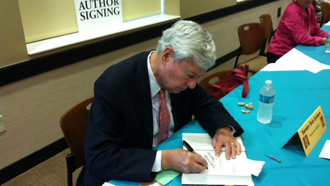 """Former Florida Senator Bob Graham signing copies of his novel, """"Keys to the Kingdom,"""" which is partially based on information he had access to as co-chair of the inquiry into the 9/11 terrorist attacks."""