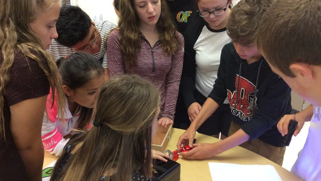 """Delsea Regional Middle School students work together to problem solve during a """"Breakout"""" session. During """"Breakouts,"""" students are challenged to decipher clues and open locked boxes within the confines of the classroom."""