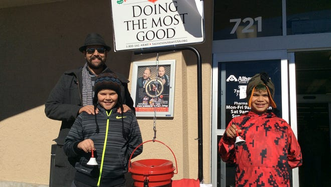 Cornerstone Bakery Cafe owner Steve Gomez and his sons Austin and Aiden  ring the bell for the Salvation Army's Red Kettle campaign in front of Albertson's Market.