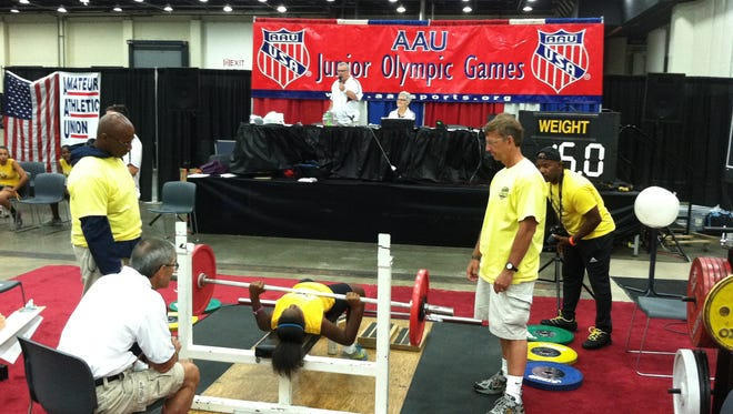 A young weight-lifter compets in the 2013 AAU Junior Olympic Games