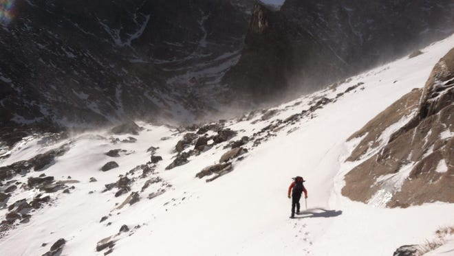 A Rocky Mountain National Park Search and Rescue team member traverses a snowfield above Peacock Pool toward Chasm Lake Tuesday during a search for a hiker who went missing while climbing Longs Peak Sunday.
