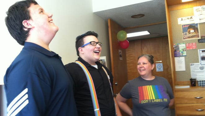 Will Daniels, 12, of Ames, Lukas Daniels, 15, of Ames and April Anderson of Ames converse and laugh in the new Des Moines Pride Center.