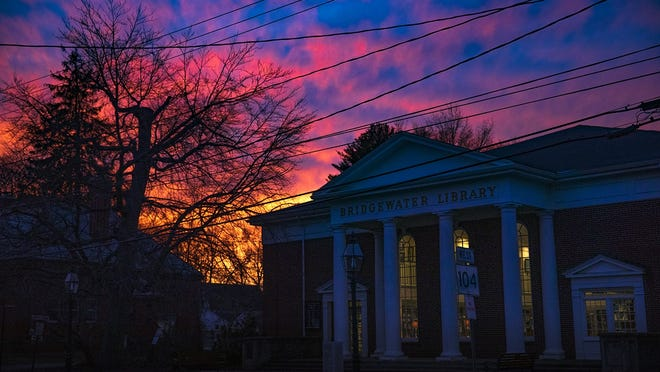 A colorful sunset is seen over the Bridgewater Public Library from Bridgewater common on Monday, Jan. 28, 2019.