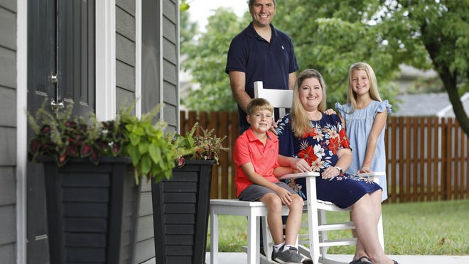 Topeka resident Jennifer Kidd sits outside her home with her husband, Kurt; son Elliott, 7; and daughter Emily, 9. Jennifer Kidd has been cancer-free for nearly six years after being diagnosed in 2014 with triple negative breast cancer. Kidd, who works as a reading and math intervention teacher at Jay Shideler Elementary, said she uses her personal story to help inspire her students to overcome their challenges.