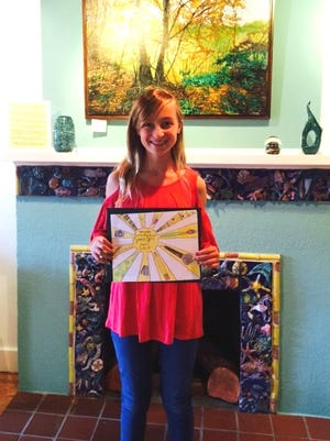 Emily Sandt is pictured during the Second Friday opening reception, held on September 8, proudly holding her winning logo design.