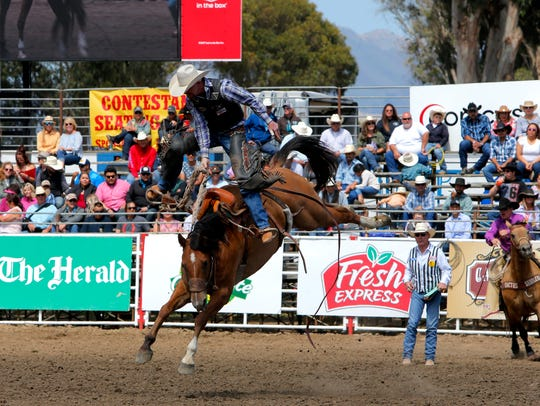 Dylan Henson competes in saddle bronc riding at the
