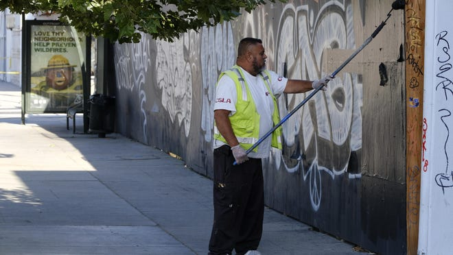 A city worker paints over tagged shop fronts along Melrose Bouvelard after mass demonstrations broke into shops looting Saturday night over the death of George Floyd in the Fairfax district of Los Angeles, Monday, June 1, 2020.