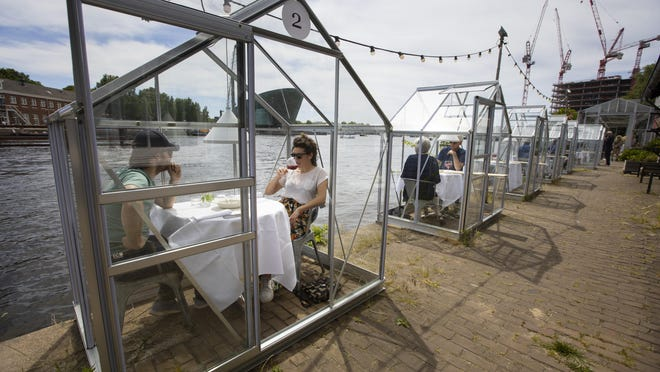 Customers seated in small glasshouses enjoy lunch at the Mediamatic restaurant in Amsterdam, Netherlands, Monday, June 1.