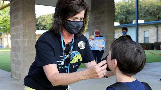 Marla Needham, Raymond Orr Interventionist, helps a student place a facemask on before entering the school, Monday, August 24, 2020, during the students first day of the 2020-21 school year in Fort Smith.