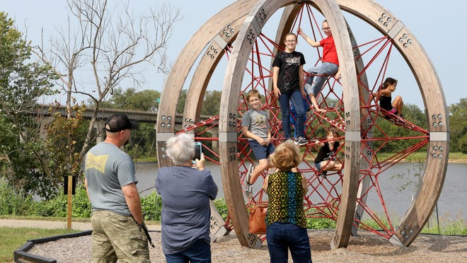 Dustin Fimpel, from left, looks on as Kim Fimpel and Mel Mooneyham video children climbing the Berliner Globe at   Fort Smith Riverfront Park, Saturday, Sept. 19.