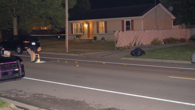 A crime scene investigator marking the crime scene of a shooting Tuesday at the 200 block of South McKenzie Street in Adrian.