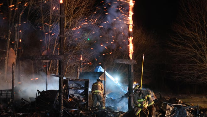 Firefighters pick apart rubble and put out hotspots Thursday among the remains of a barn that contained an estimated 20,000 books next to the Read It and Reap Library in Sand Creek was destroyed by fire.