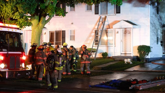 Firefighters assemble in front of a house on North Broad Street in Adrian after a fire early Saturday.