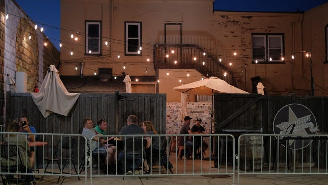 Diners enjoying drinks and food at Tecumseh Brewing Company in downtown Tecumseh Monday.