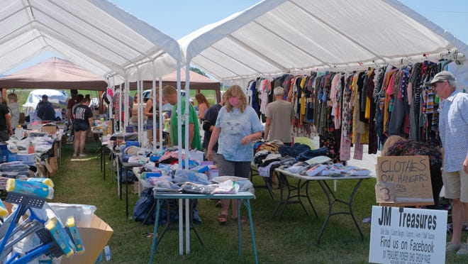 Canopies are set up along U.S. 127 by the Pioneer, Ohio-based JM Treasures Saturday for the U.S. 127 Yard Sale as customers, masked and unmasked, look through the vast array of items.