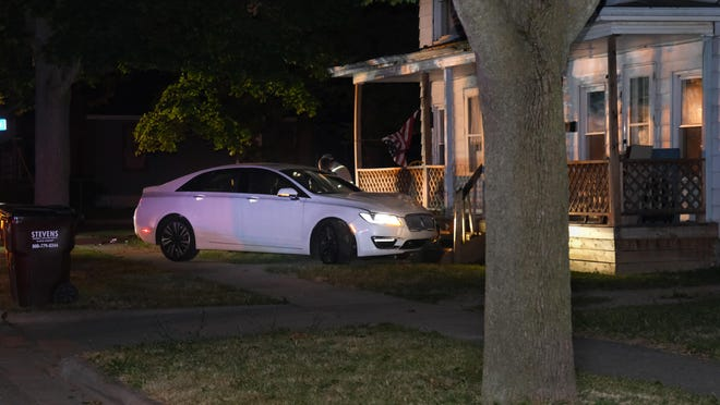 A Lincoln MKZ that was stolen from Bell Ford early Tuesday morning, crashed into the porch of a house at the intersection of McVicar and Toledo streets in Adrian after a chase with police.