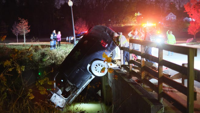 Employees of Affordable Towing evaluate the situation of a Cadillac Escalade that crashed through the guardrail of the entrance bridge at Island Park Friday in Adrian.