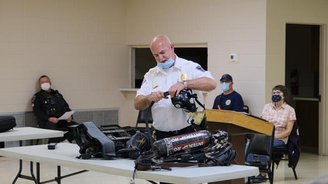 Raisin Township Fire Chief Jim Hannah demonstrates a connection between a mask and air tank at a meeting of the Raisin Township Board Monday when he requested the purchase of 19 new air packs for the department.