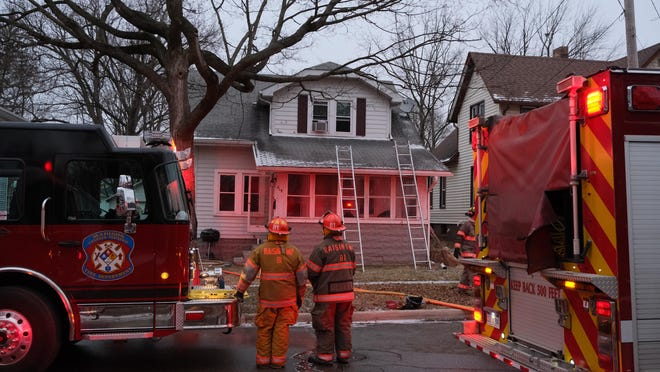 Firefighters overseeing the clearing of a house on the 800 block of East Hunt Street in Adrian after a fire in its first floor Sunday.