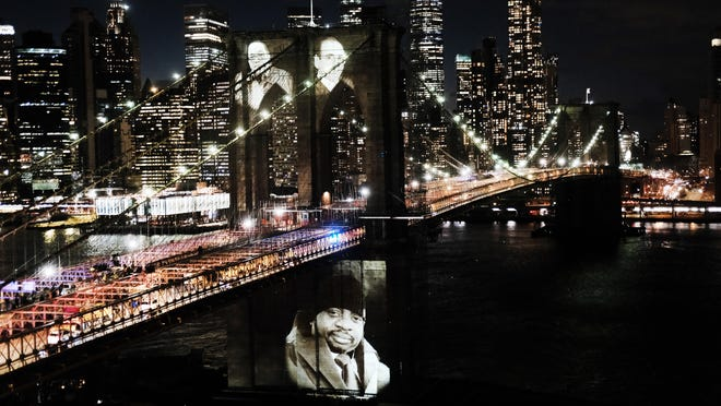 """Faces of victims of COVID-19 from New York City are projected onto the Brooklyn Bridge on Sunday during a memorial service called """"A COVID-19 Day of Remembrance."""""""