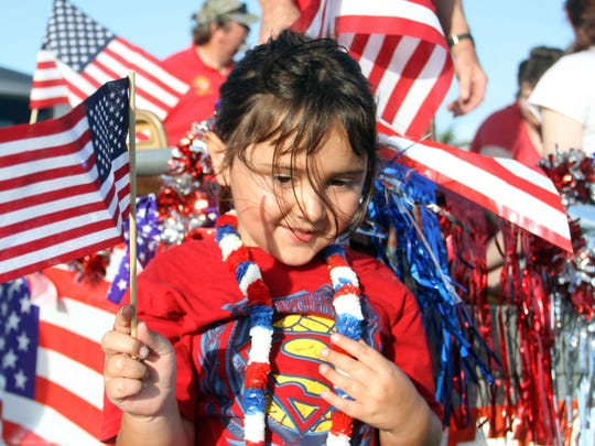 Lily Hughes, 6, waves the flag before the San Carlos Park parade in 2014.
