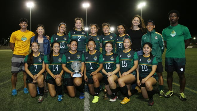 The University of Guam women's soccer team poses for a photo with the champions trophy of the Bud Light Women's Soccer League W2 Division after winning the division's title match 4-2 against ISC/Calvo's SelectCare Team Slay Sunday evening at the Guam Football Association National Training Center. In the photo are, kneeling, from left to right, Veronica Dydasco, Ashley Borja, Koholali'i Maertens, Elisha Benavente, Mellanne Rasmussen, Jestyne Sablan, and Shaeina Torres. In the back row, standing from left to right, are UOG coach Dylan Naputi, GFA Women's Committee Member Annette Roberto, Aiyana Shedd, Aubrey Yatar, Aiesha Castro, Philana Lopez, Ariya Cruz, GFA Women's Committee Member Yvonne San Nicolas, UOG coach Rod Hidalgo, and UOG coach Jacques Diambra-Odi.