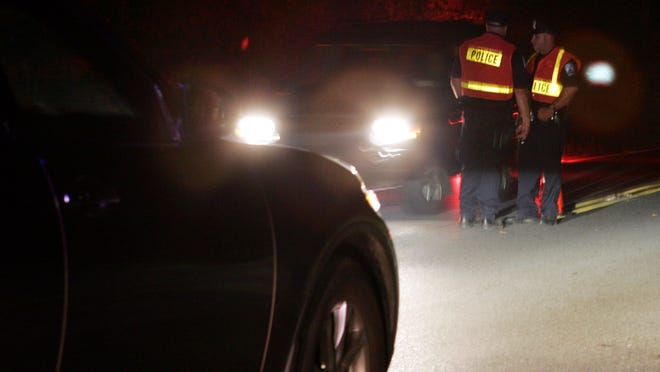 Police conduct a driving while intoxicated checkpoint in this file photo.
