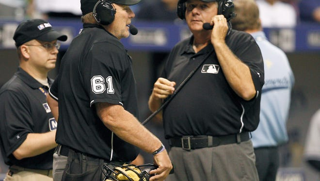Umpire Bob Davidson (61) and Jerry Lane wait for a response on an instant replay review.