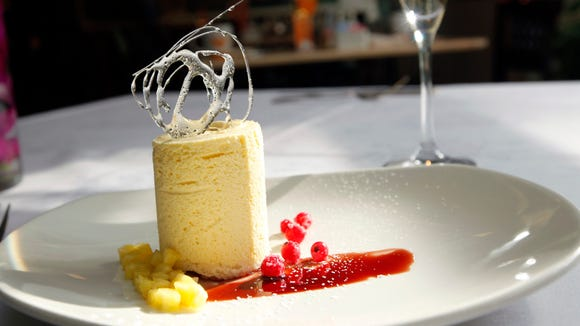 Frozen Passion Fruit Souffle' with Spiced Red Wine, Pineapple Confit and Candied Currants at the Orchids at the Hilton Netherland Plaza.
