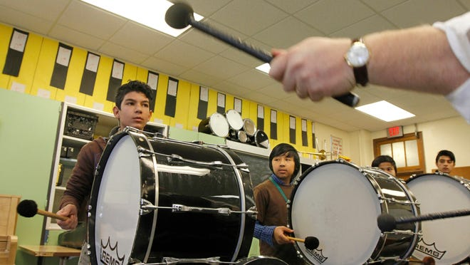 Eighth grader Haidar Al Hasooni, left, keeps close watch as he waits for his signal to start from Mike Hillman, music and band teacher, last month during the bass drum ensemble practice at Rochester International Academy. The group is playing five bass drums that were recently donated to the school.