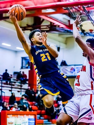 Malek Adams ,21, of Grand Ledge is fouled by Devon Taylor ,right, of Sexton as he takes the ball to the Sexton basket with less then 1 minute remaining in their game.  Adams would sink 1 of 2 freethrows to put Grand Ledge up 58-56.
