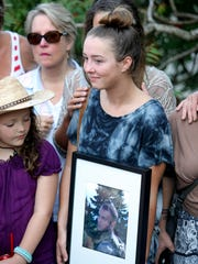 Genna King holds a photo of her brother during the sign dedication ceremony.