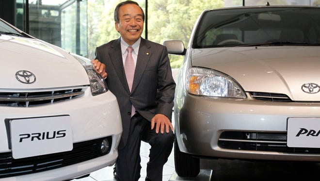 Takeshi Uchiyamada, vice chairman of Toyota Motor Corp., poses for a photo with first, seen at right, and second model of Prius at its headquarters in Tokyo, Wednesday, April 17, 2013.