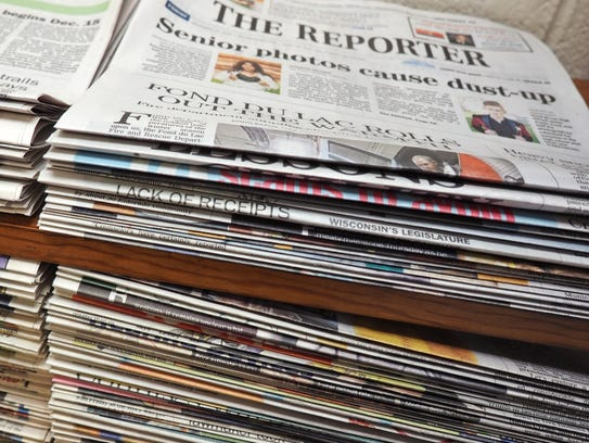 A stack of The Reporter and a stack of Action Publications
