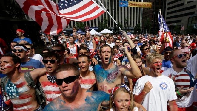Soccer fans sing the National Anthem at the start of a World Cup match between the United States and Belgium being viewed on a large screen television on Tuesday, July 1, 2014, on Fountain Square in downtown Cincinnati.