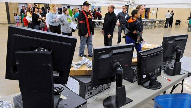 People wait in line to receive their computers from PCs for People on Friday at the St. Cloud Armory. The St. Paul-based nonprofit organization distributed computers to 200 local families.