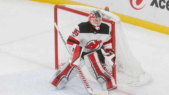 New Jersey Devils goalie Cory Schneider defends the net against the Minnesota Wild in the first period of an NHL hockey game Monday, Nov. 20, in St. Paul, Minn. (AP Photo/Jim Mone)