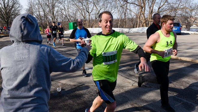 A runner takes a drink of water along the course of the Earth Day Half Marathon Saturday, April 21, in St. Cloud.